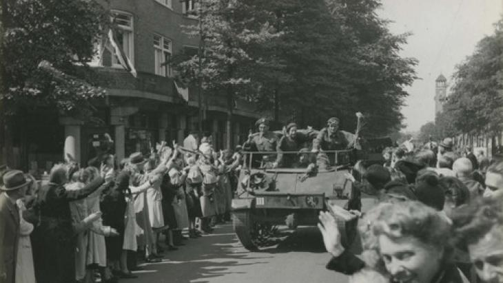 Feestende mensen zwaaien naar de bevrijders in 1945.