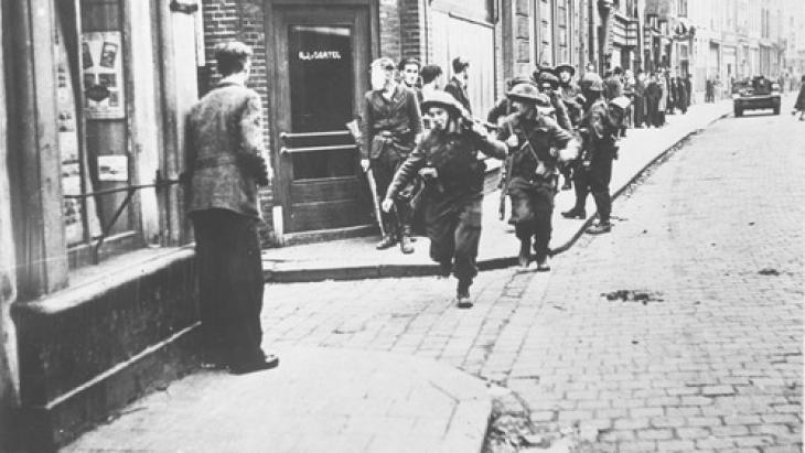 Soldaten steken een straat over in Den Bosch. Ze moeten oppassen voor Duitse sluipschutters.
