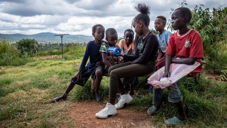 Kinderen in Kenia luisteren met z'n allen naar een radio op batterijen.