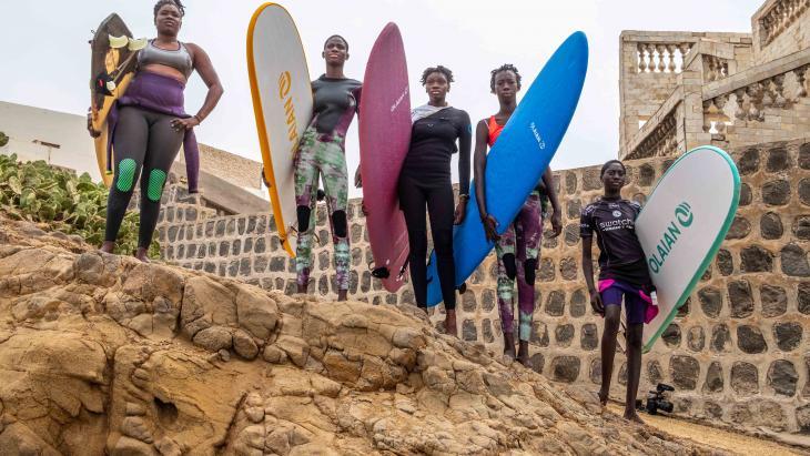 Khady (met blauwe surfboard) uit Senegal wil surfkampioen worden.