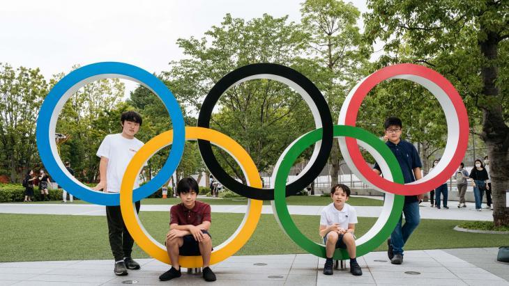 Vier vrienden uit de Japanse stad Tokio poseren bij de Olympische ringen.