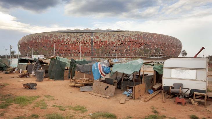 Dit is het Soccer City Stadium voetbalstadion in Johannesburg. Hier wordt de WK-finale gespeeld. Op de voorgrond zie je tijdelijke huisjes van arbeiders die aan het stadion werken.