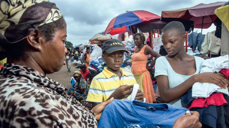Dennis en Suzy shoppen tweedehands kleding op de markt in Ghana.