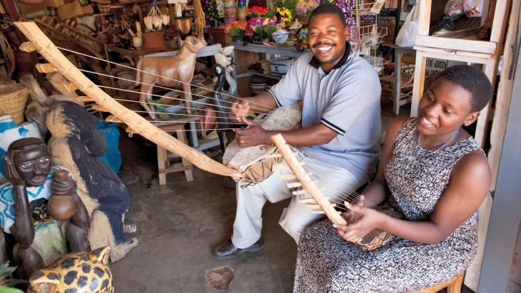 """Bridget en haar vader spelen op een Ugandese harp. """"Ik zing met mijn vader in het kerkkoor."""""""