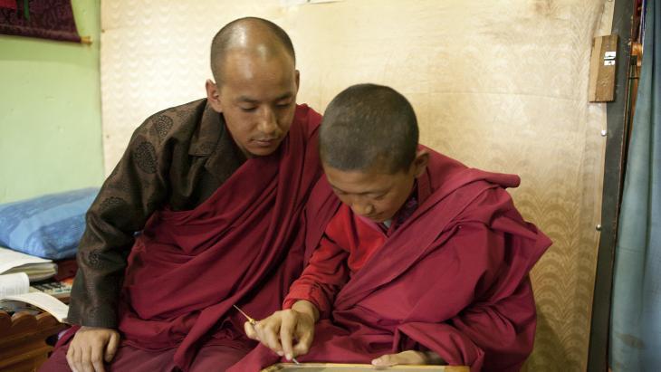 Khandu Wangchuk oefent astrologische nummers onder het toeziend oog van de meester