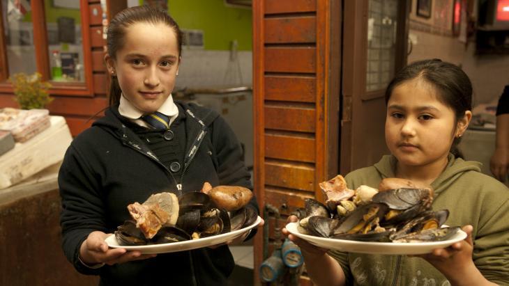 Natalie (r) en Joselin met twee dampende borden curanto.
