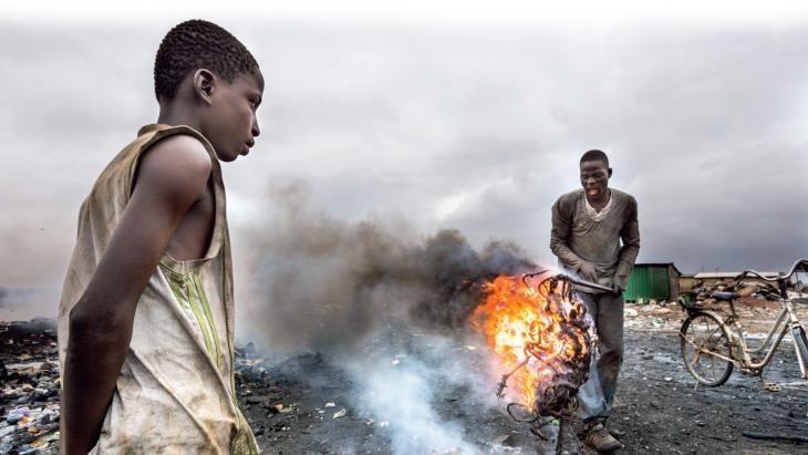 Yaw kijkt naar een oudere jongen die kabels verbrandt.