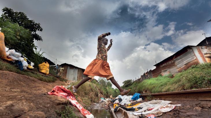 Night springt over een open riool; een geul met afvalwater en huisvuil.