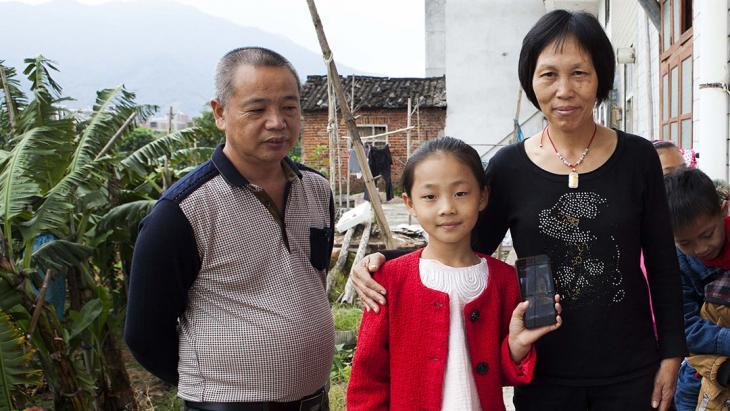 Xin Ya woont op het platteland van China bij haar grootouders. Op de telefoon laat ze een foto van haar moeder zien.