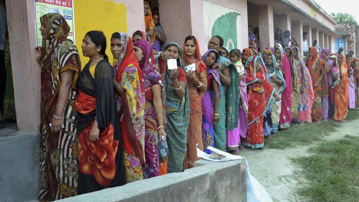In India staat een lange rij vrouwen klaar om te stemmen.