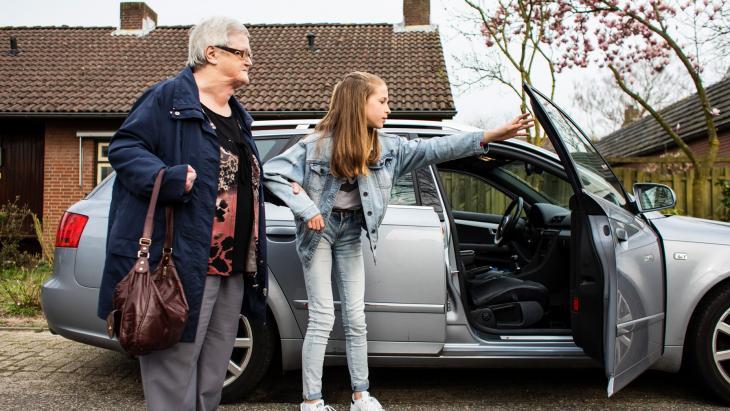Mijntje ondersteunt haar buurvrouw Cella van de voordeur naar de auto.